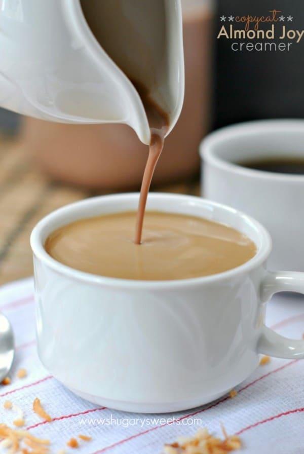Homemade almond joy coffee creamer being poured into a mug of coffee.