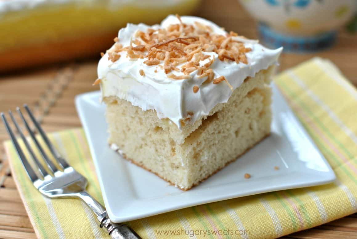Slice of coconut pudding cake on a white plate and topped with toasted coconut.