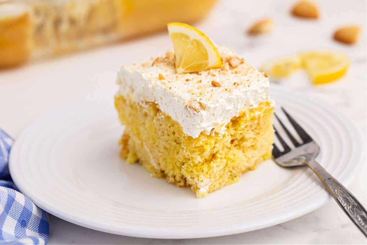 Slice of lemon cake topped with lemon jello and whipped cream.