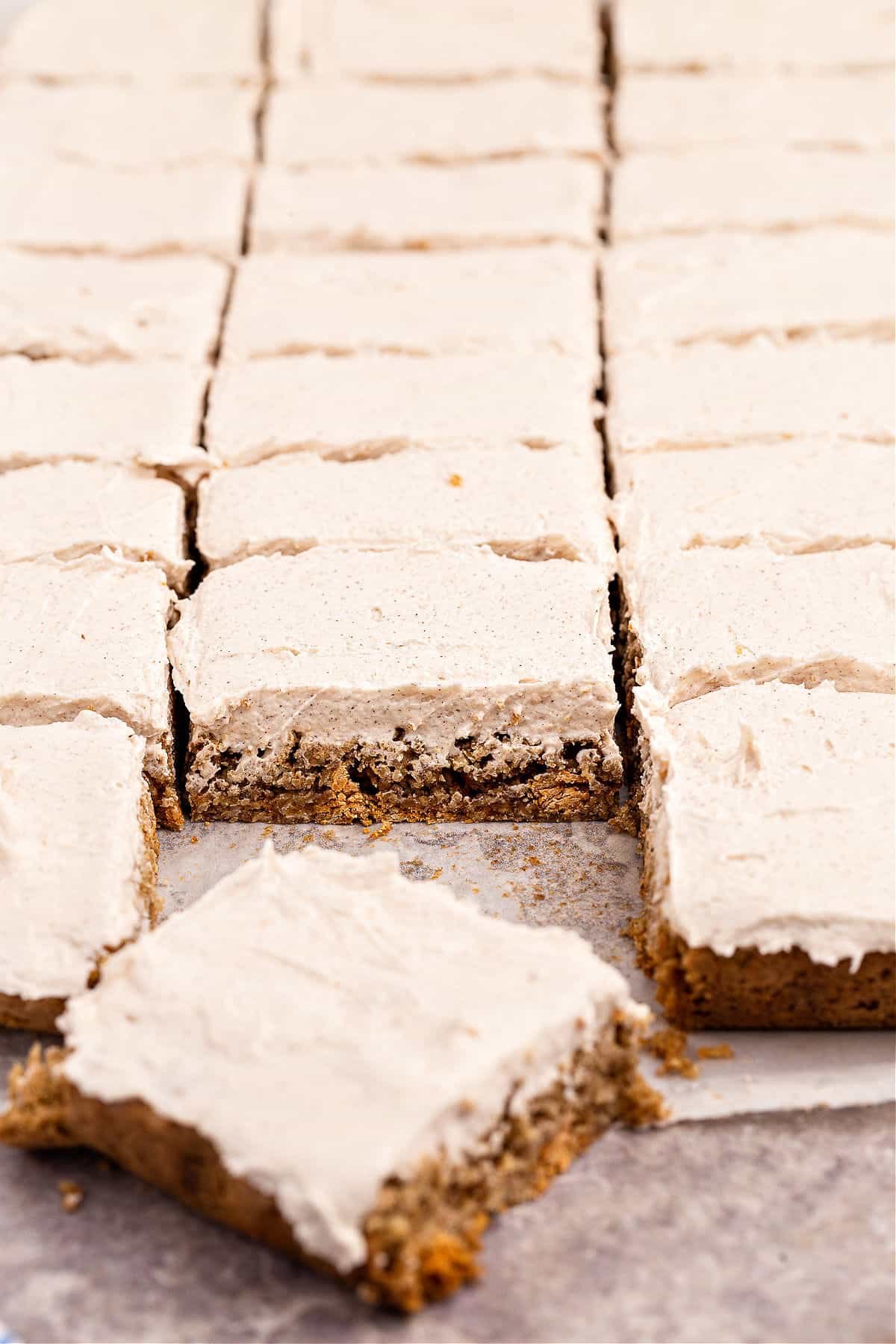 Oatmeal butterscotch cookie bars topped with cinnamon frosting and cut into squares.