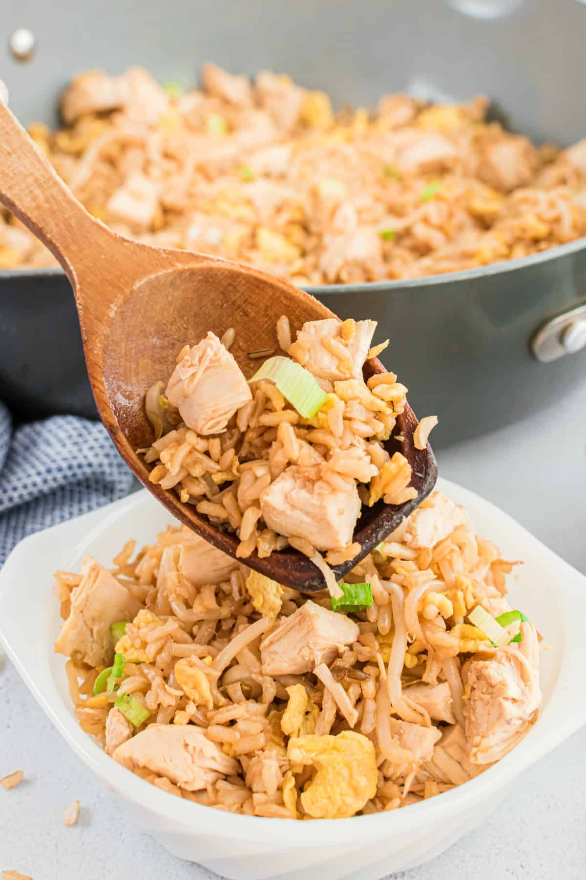 Chicken fried rice being spooned into a white bowl with a wooden spoon.