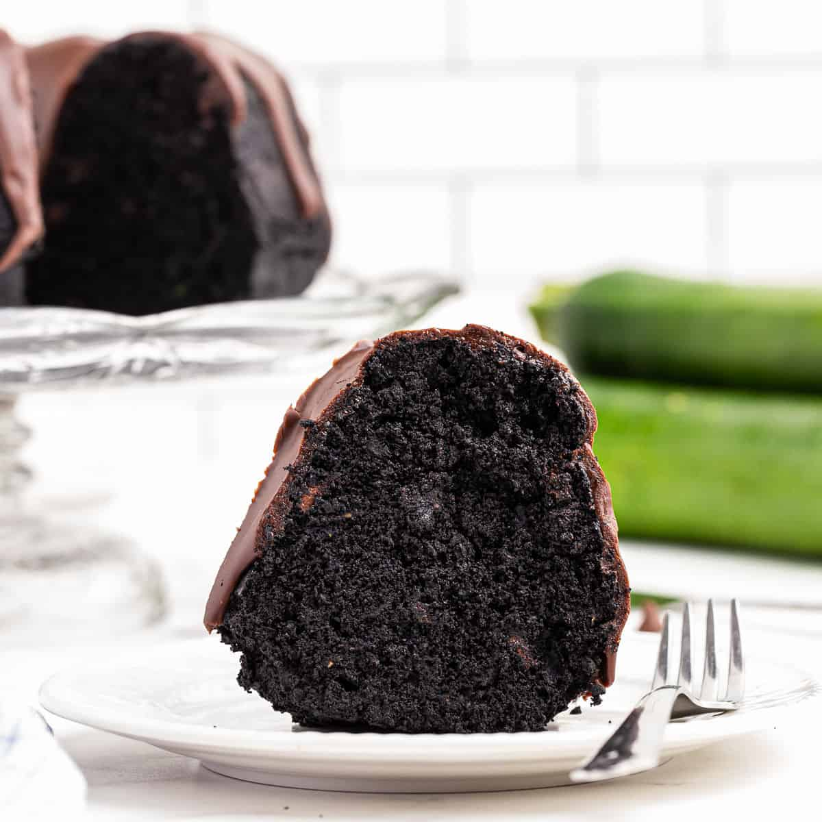 Slice of chocolate zucchini cake on a white plate.
