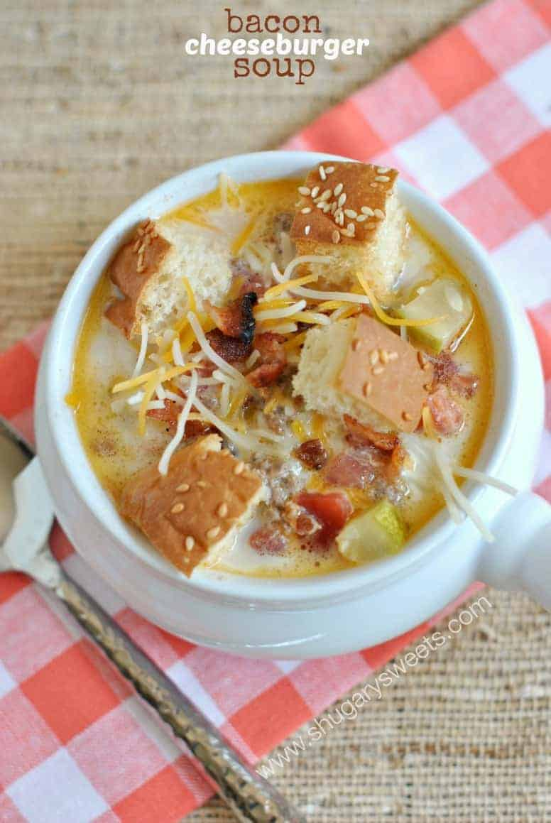 Cheeseburger soup with hamburger bun croutons in a white soup crock.