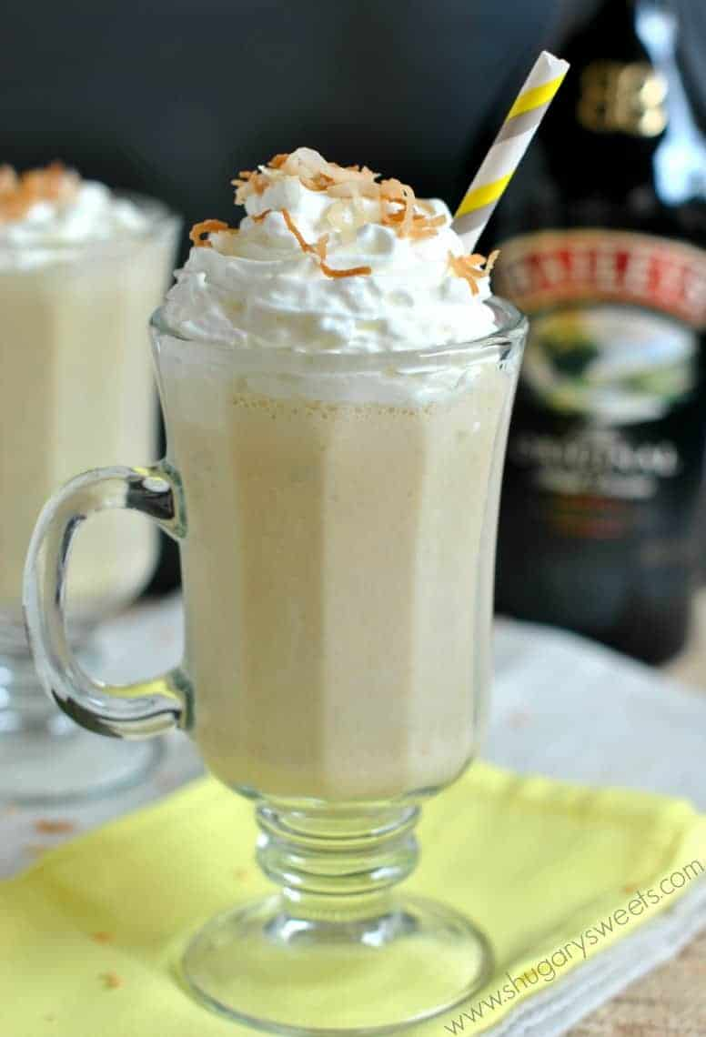 BBC drink in a clear glass mug garnished with whipped cream and toasted coconut.