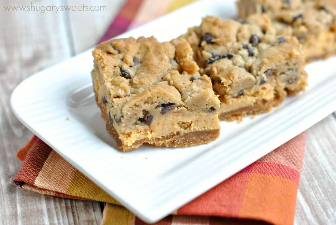 Pumpkin chocolate chip cheesecake bars on a white platter with plaid linen napkin.