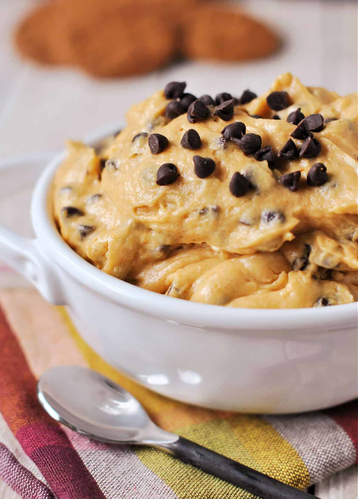 Pumpkin dip with chocolate chips in a white bowl.