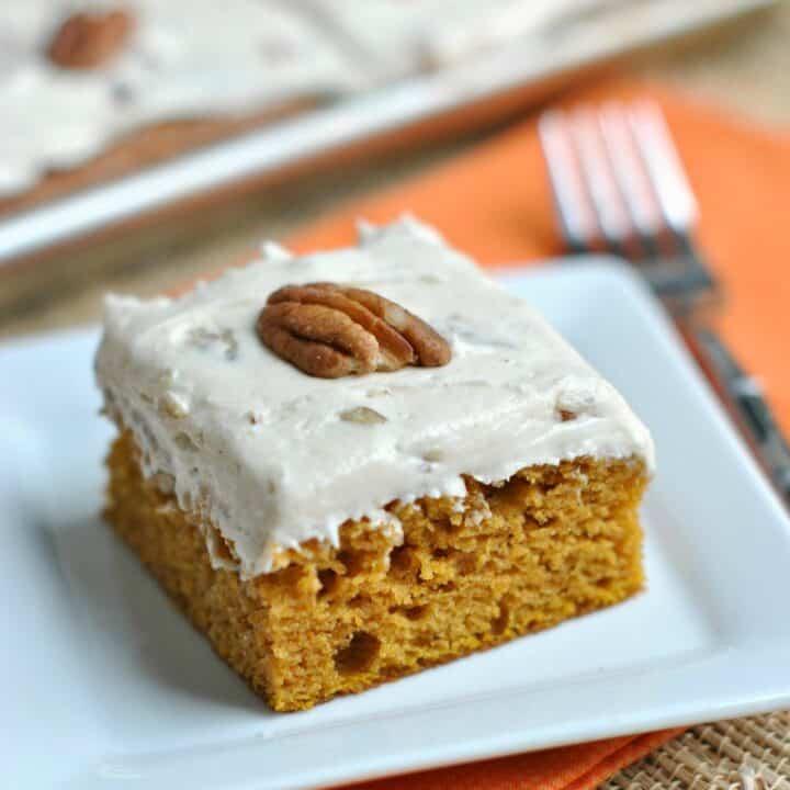 Slice of butter pecan frosted pumpkin bar on a white dessert plate.