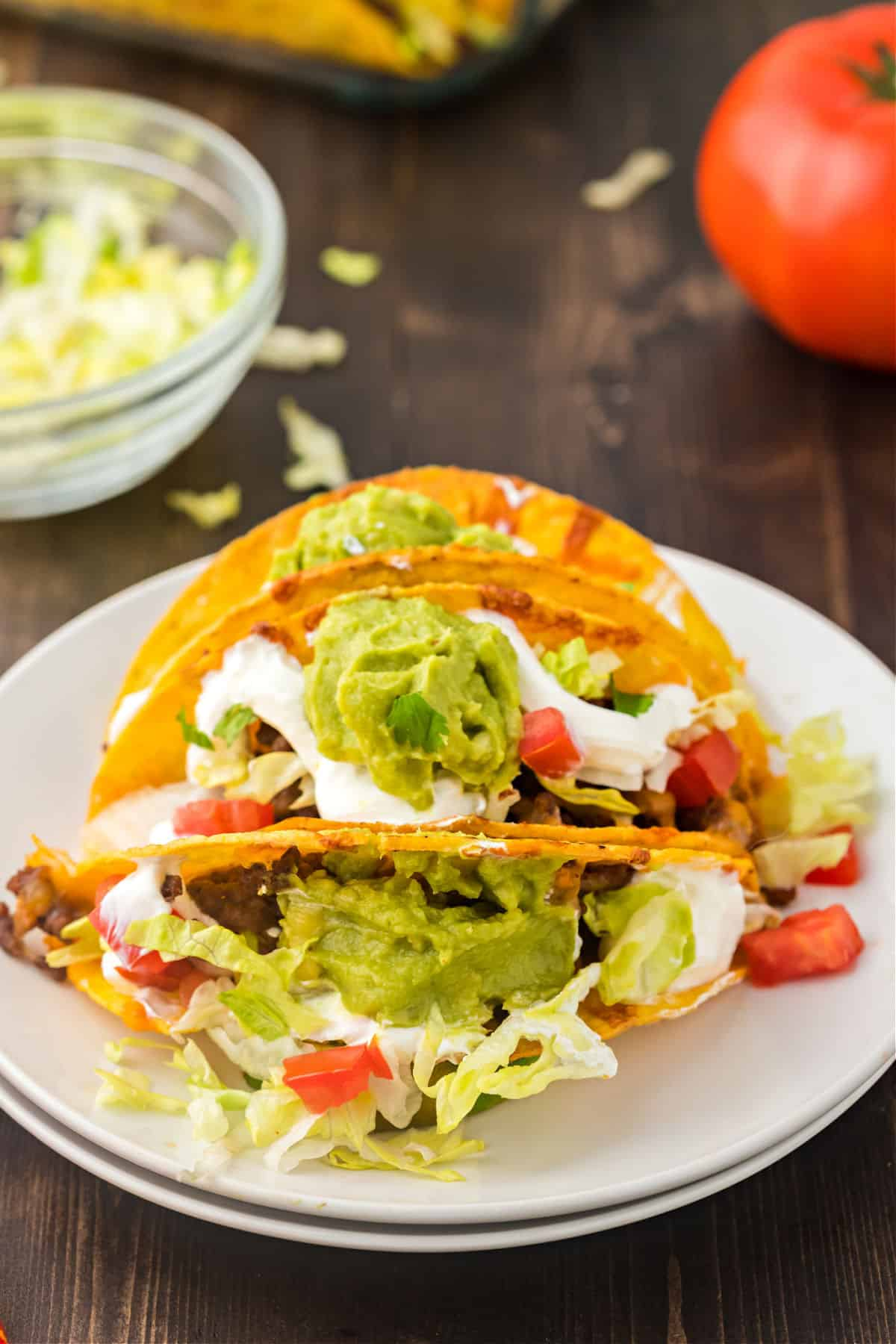 Baked tacos served on a white plate with lettuce, tomato, sour cream, and guacamole.