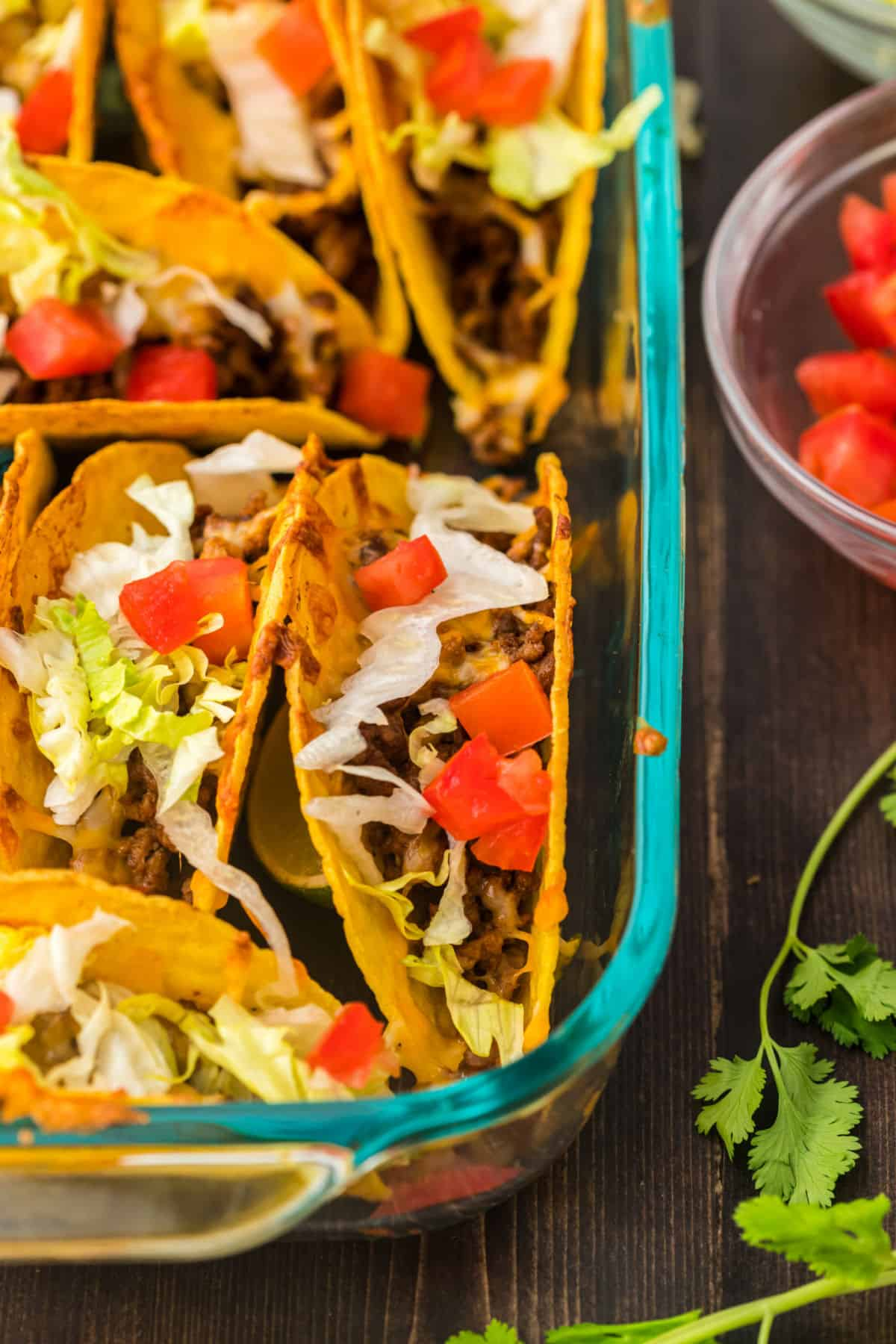 Baked tacos in clear glass baking dish,