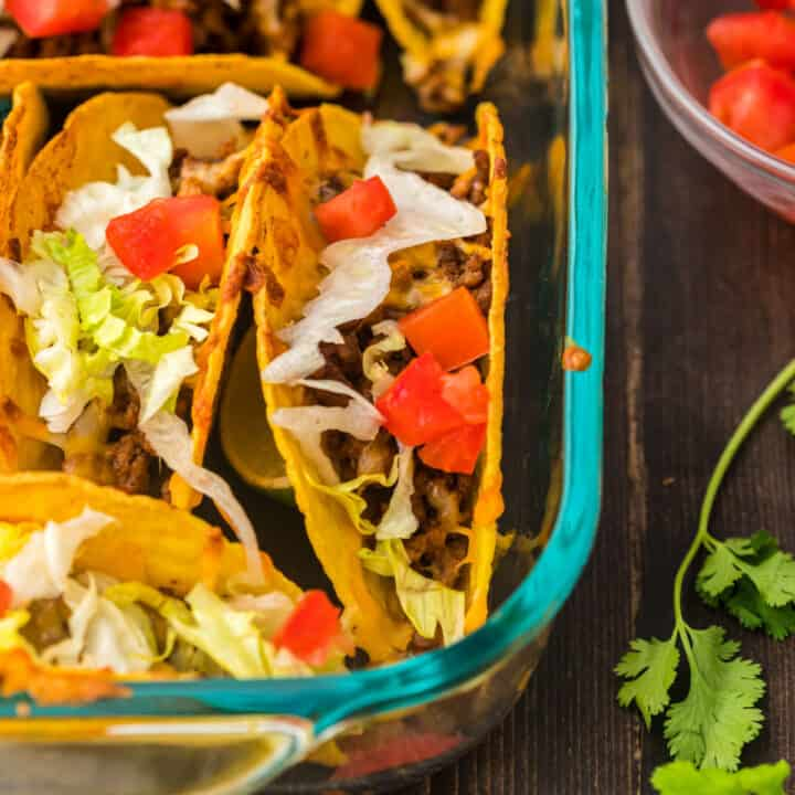 Baked tacos in clear glass baking dish and garnished with vegetables.
