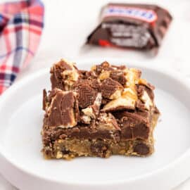 Slice of chocolate chip snickers cookie bar on a white plate.