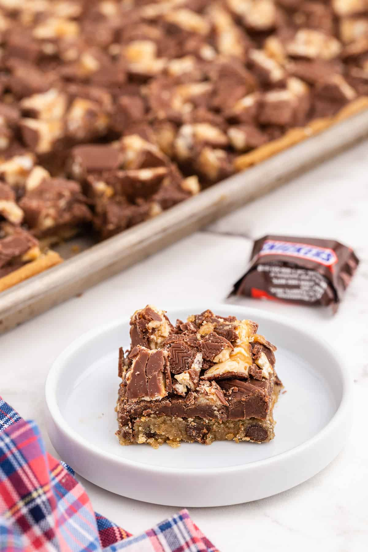 Slice of chocolate chip snicker's cookie bar on a white plate.