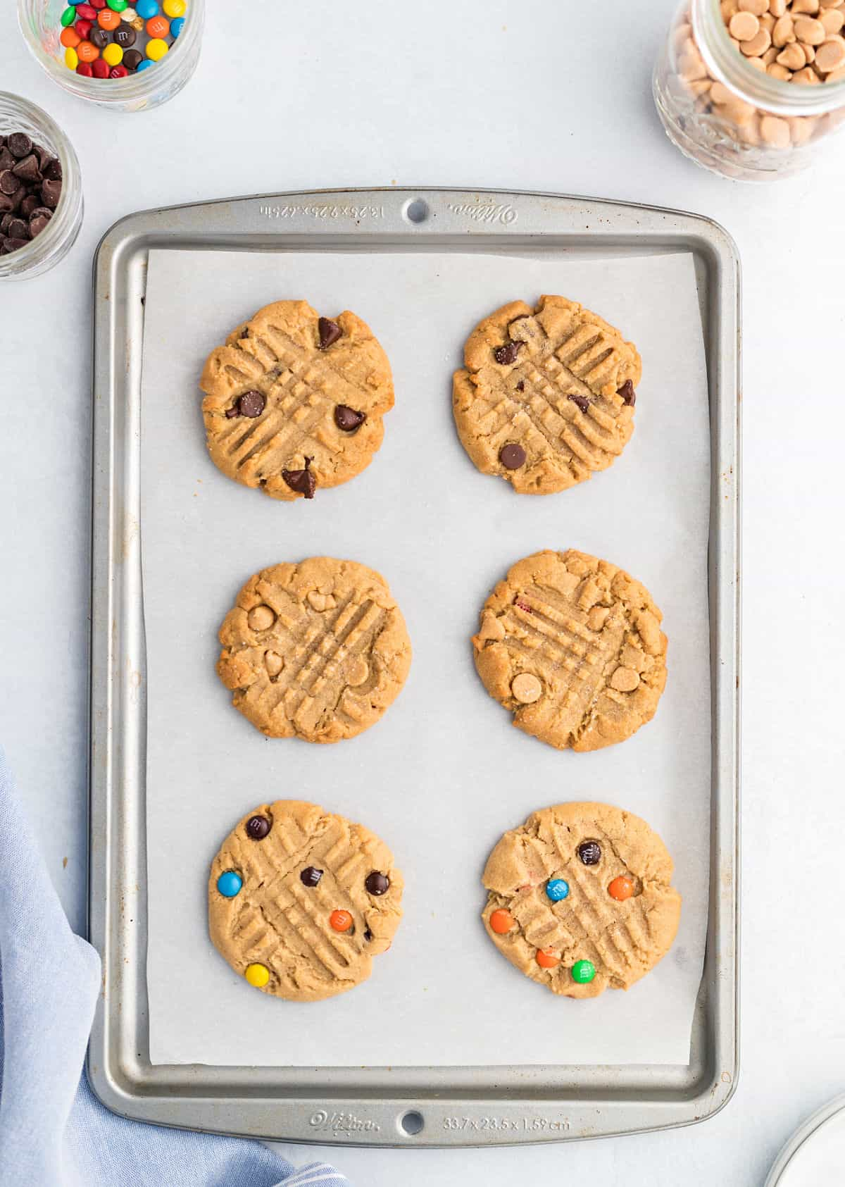 Peanut butter cookies on parchment paper lined cookie sheet.