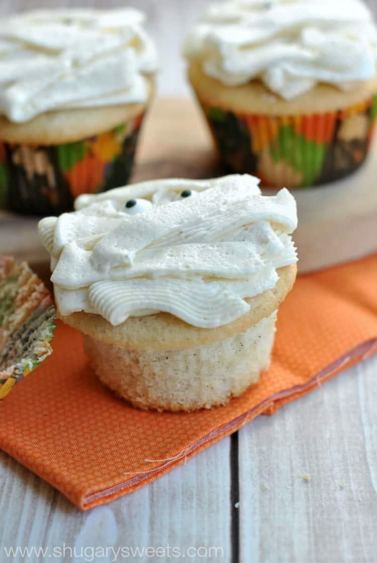 Vanilla bean cupcake unwrapped so you can see the flecks of vanilla bean.