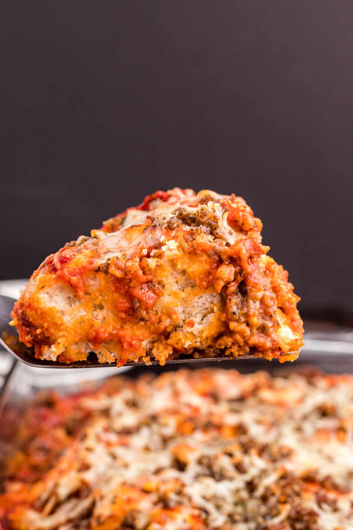 Pizza casserole being served with spatula out of baking dish.