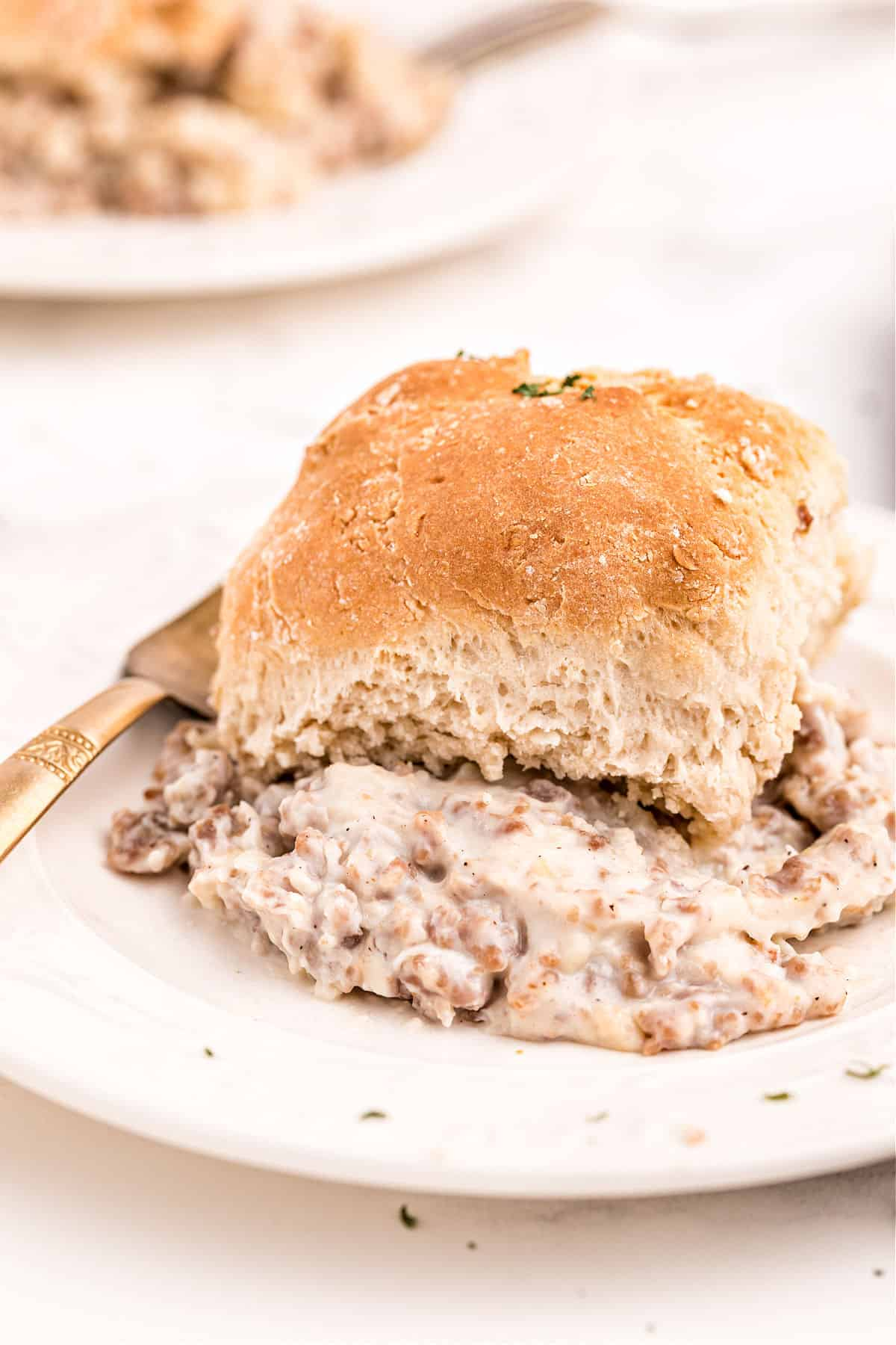 Sausage and gravy with biscuit served on a white plate.