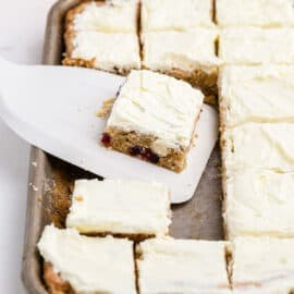 Slice of cookie bar with cranberry orange and frosting.