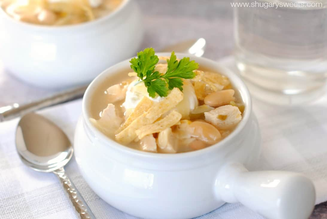 White chicken Chili topped with parsley in a white bowl and silver spoon.