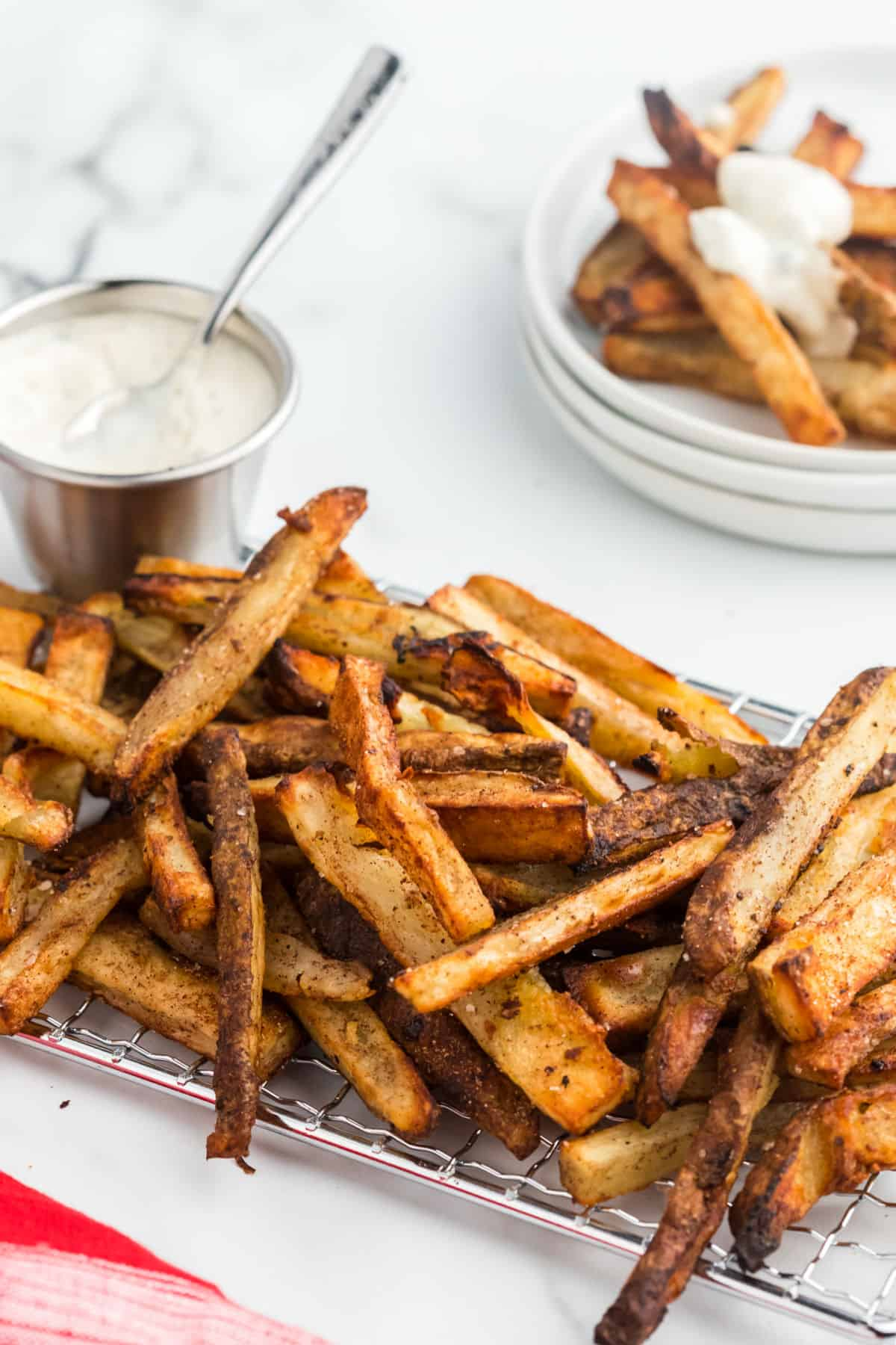 Baked french fries with a side bowl of blue cheese dressing.