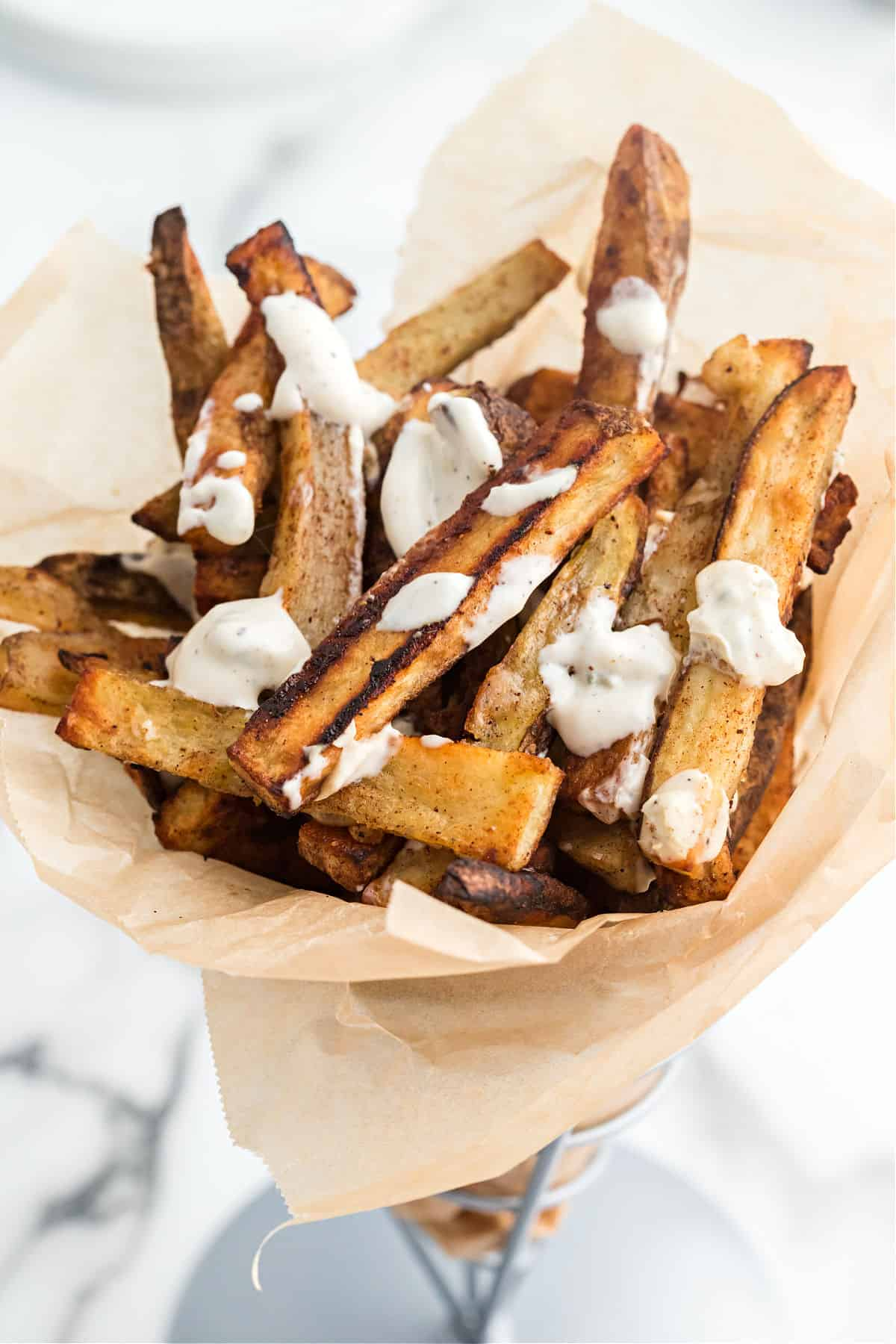 Baked french fries with bleu cheese dressing in a basket for serving.