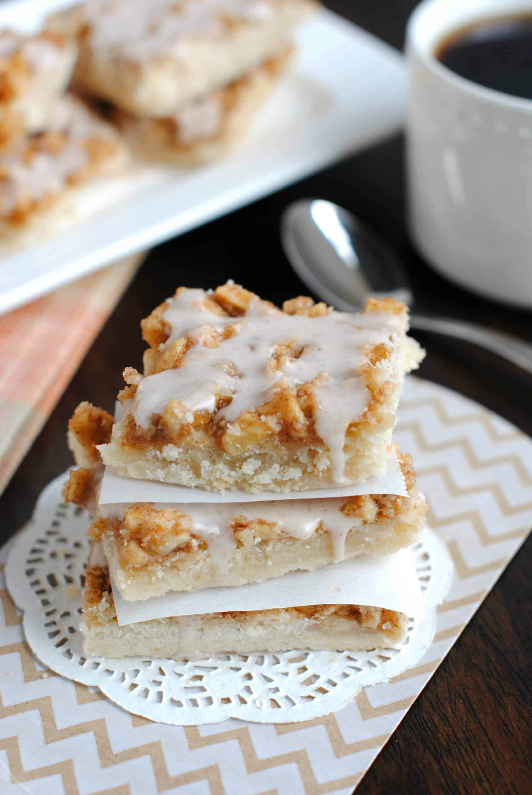 Stack of shortbread apple bars on a white doily with cup of coffee on side.