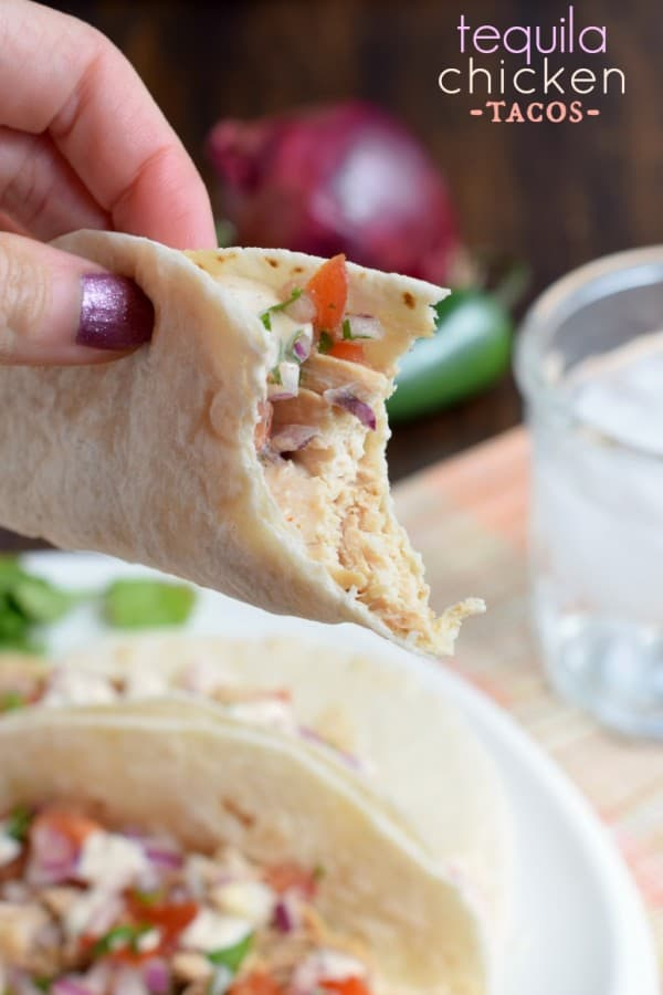 These Tequila Chicken Tacos are made in the slow cooker and topped with fresh pico de gallo and jalapeno cream!