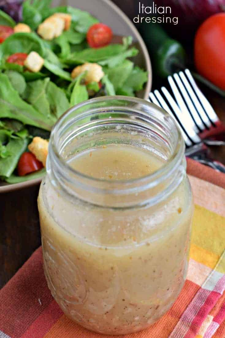 Italian dressing made from scratch in a mason jar, on a red and orange linen.