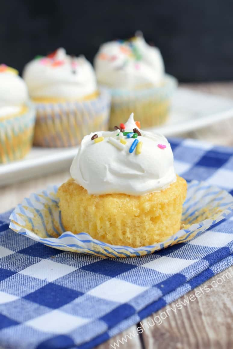 Pineapple cupcake topped with whipped cream and sprinkles unwrapped on a blue checkered napkin.