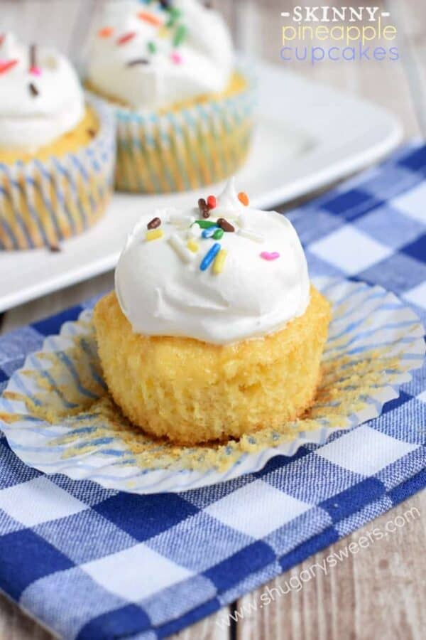 Pineapple cupcake on a blue checkered linen with the wrapper undone and topped with cool whip and sprinkles.