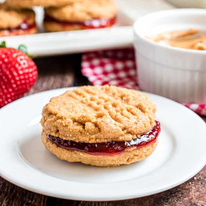 Peanut butter sandwich cookie with strawberry filling on white plate.