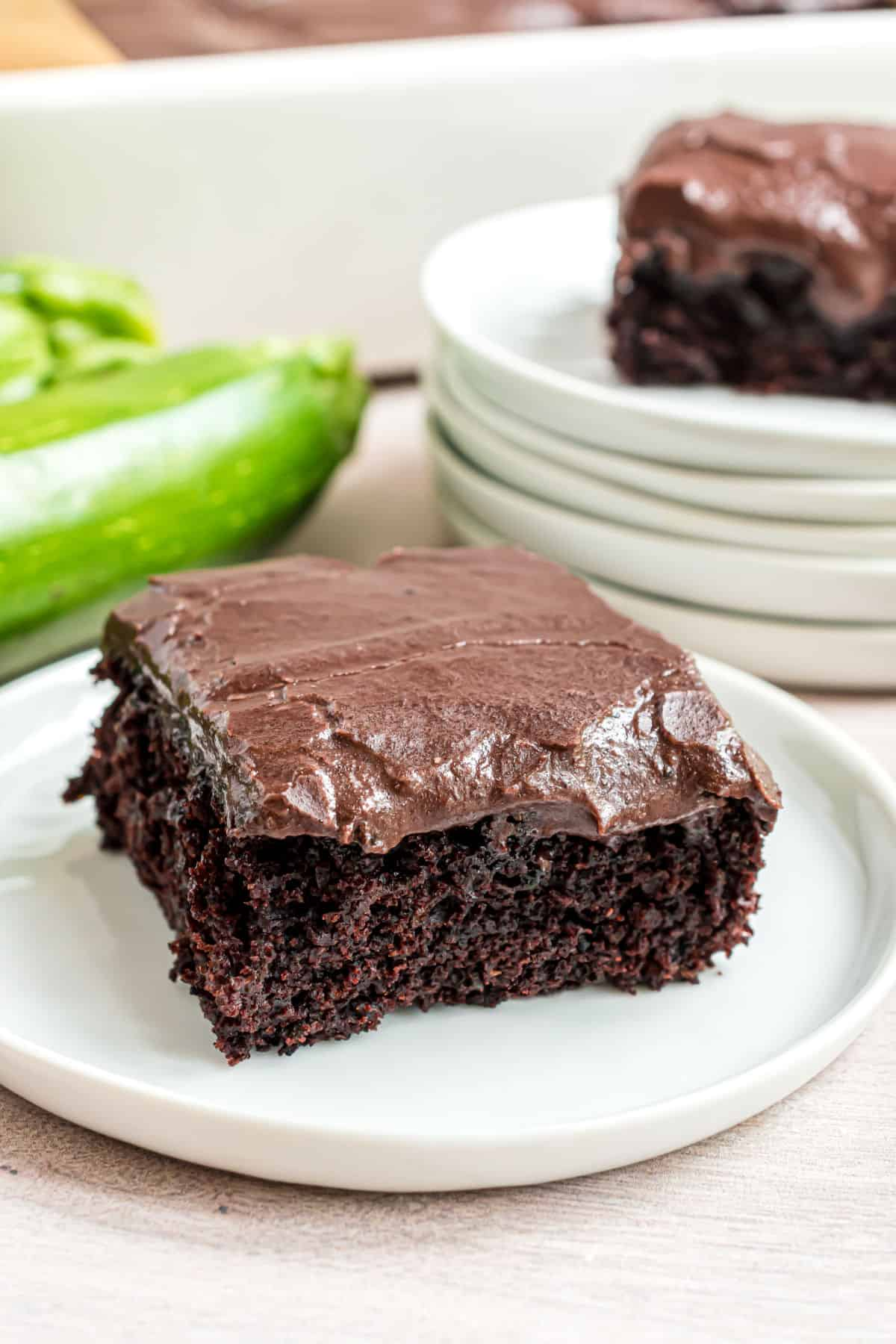 Slices of chocolate frosted zucchini brownies on white dessert plates.