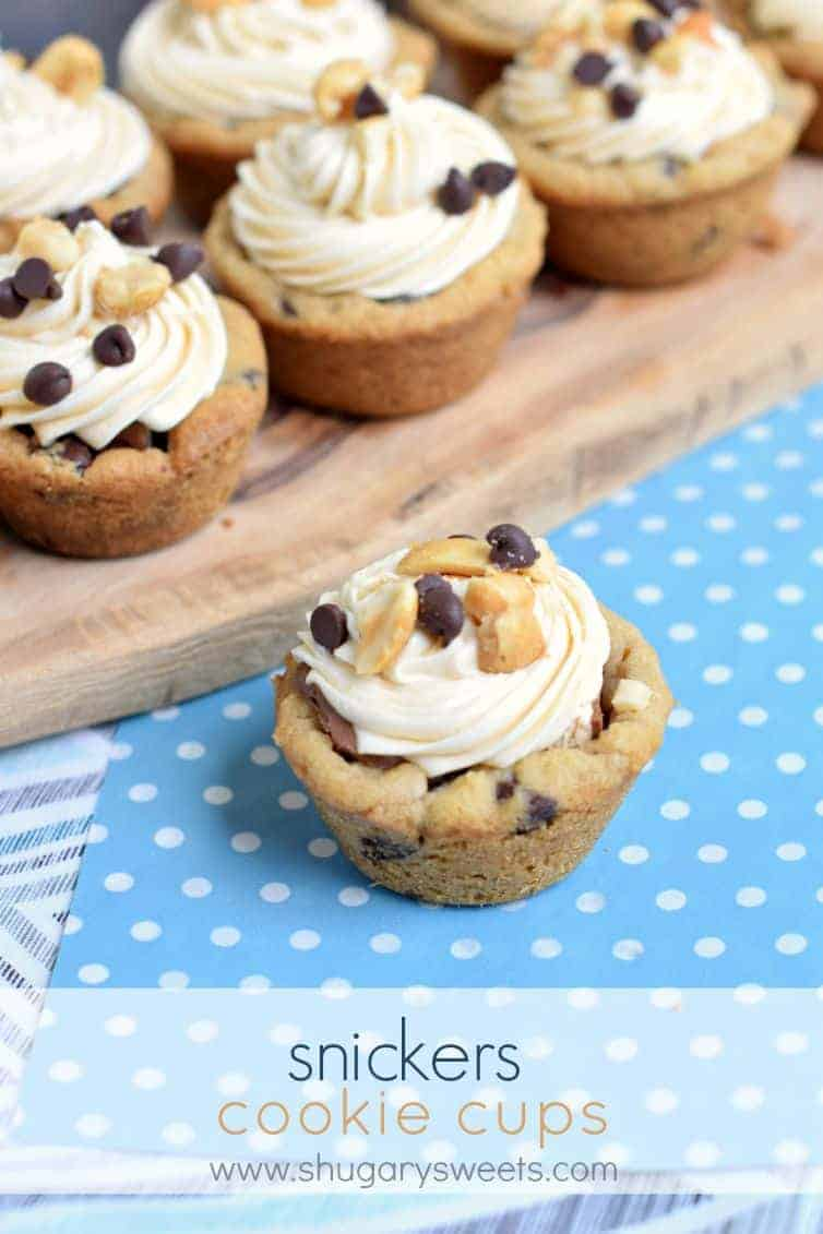 Chocolate chip cookie cups with a snickers filling and caramel frosting. On a light blue with white polka dot linen.
