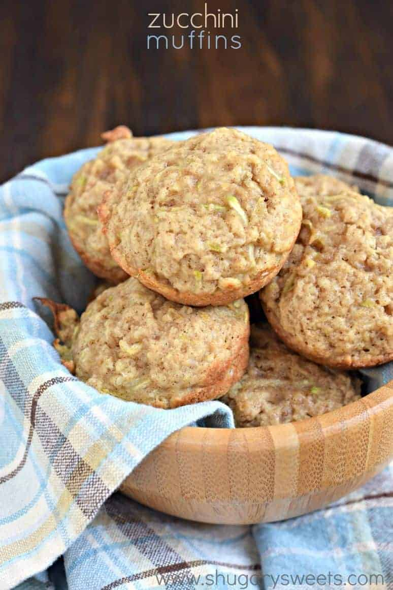 Zucchini muffins in a blue towel lined wooden bowl.