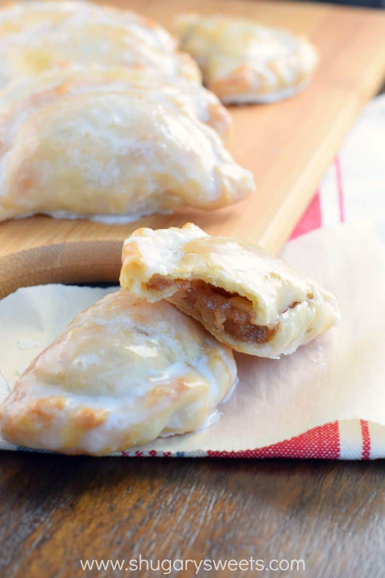 Hand pies with apple filling on a piece of parchment paper, cut open to see the inside.