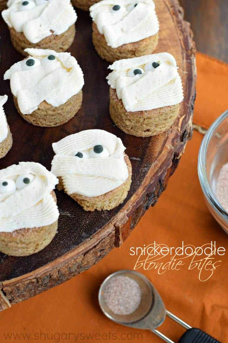 Snickerdoodle Blondie Bites with mummy frosting on a wooden cake stand.