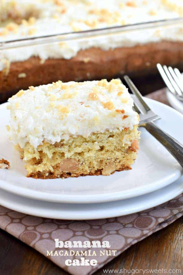 Slice of banana macadamia nut cake topped with buttercream on a white plate.