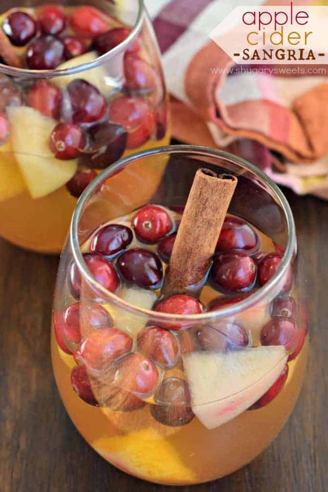 Apple cider sangria in a stemless wine glass with fresh apples, cranberries, and cinnamon stick.
