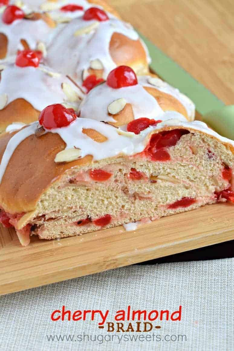 Loaf of cherry almond bread with almond glaze on wooden platter.