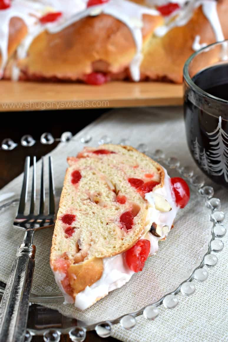 Slice of cherry almond braid on clear glass plate.