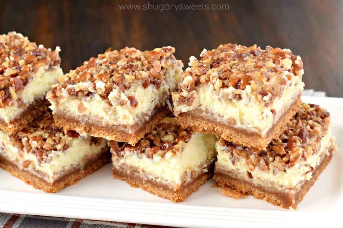 Pecan Pie Cheesecake bars on a white serving plate.