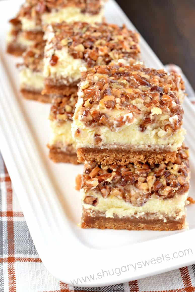 Pecan pie cheesecake layered bars on a white serving dish.