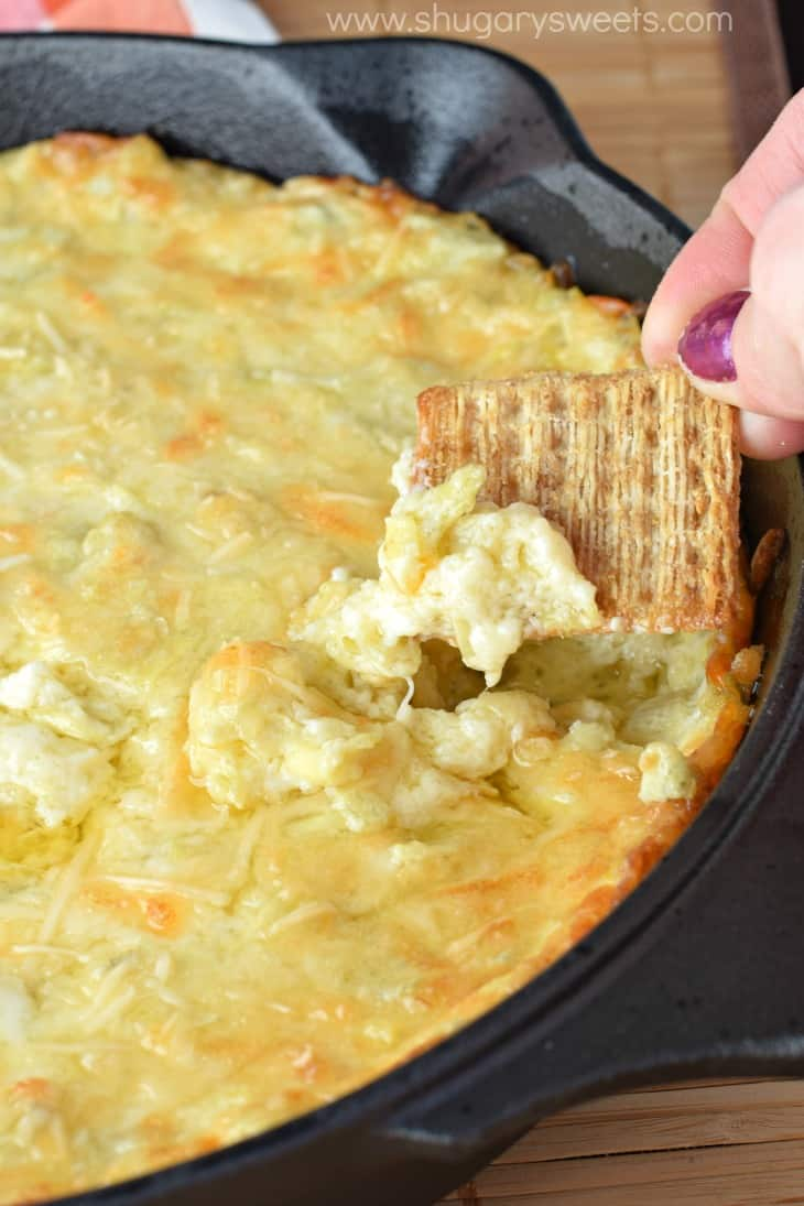 Hot artichoke dip in a cast iron skillet scooped up with Triscuits.