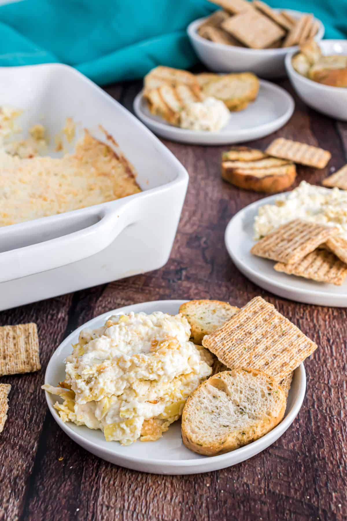 Artichoke dip served on a plate with triscuits and hearty bread pieces.