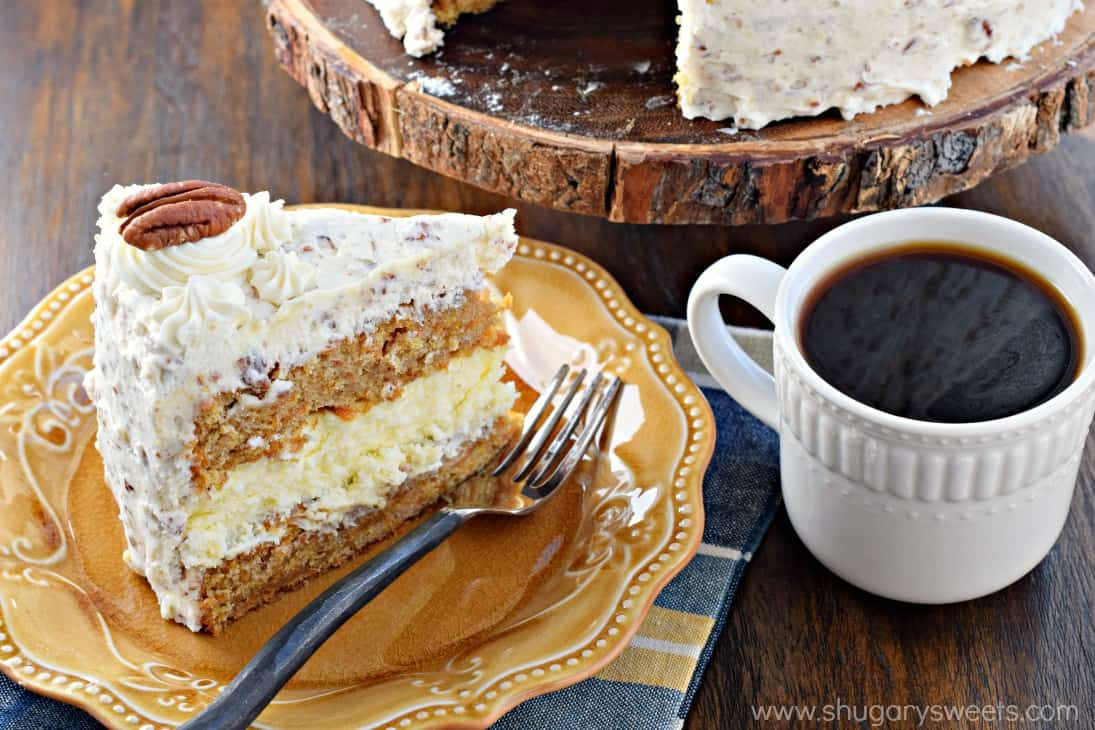 Carrot Cake Cheesecake Cake with cream cheese frosting and pecans on a yellow plate with mug of coffee.