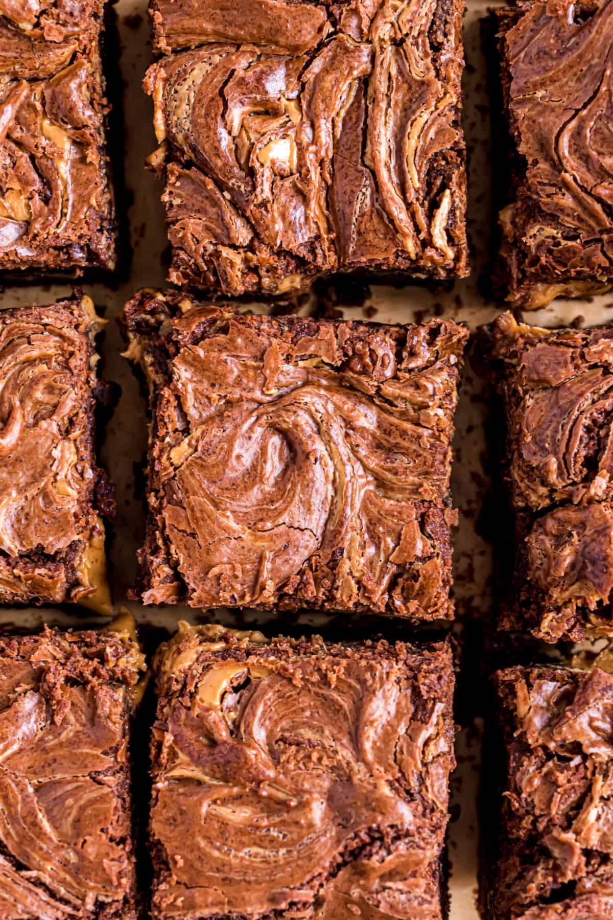 Squares of peanut butter swirled brownies on a parchment paper baking sheet.