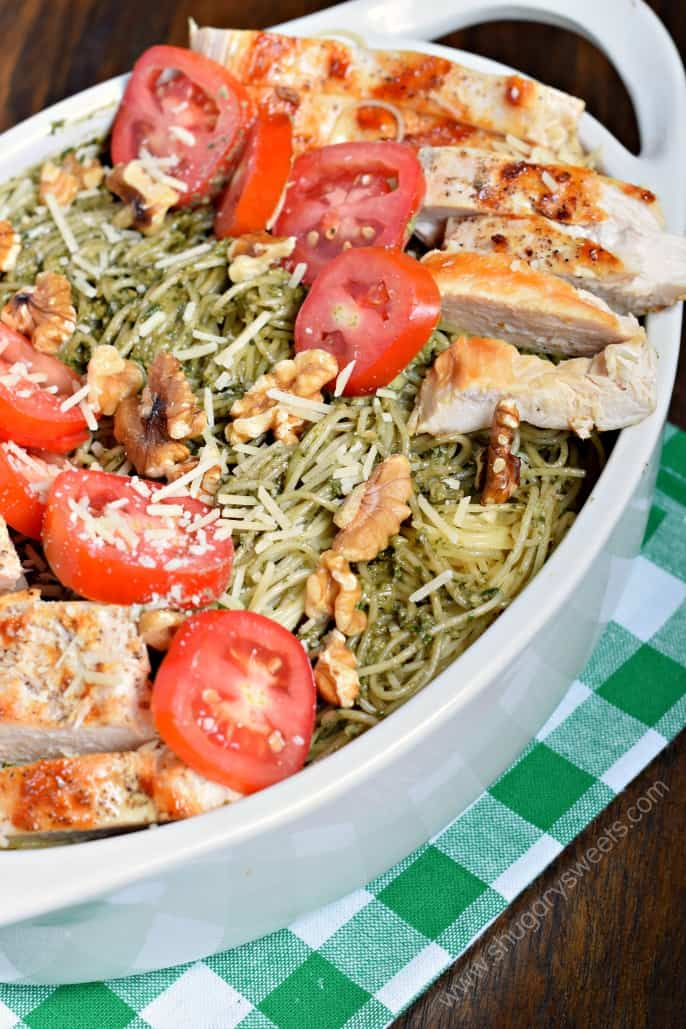 Pesto Pasta in a baking dish with chicken, tomatoes, and walnuts.