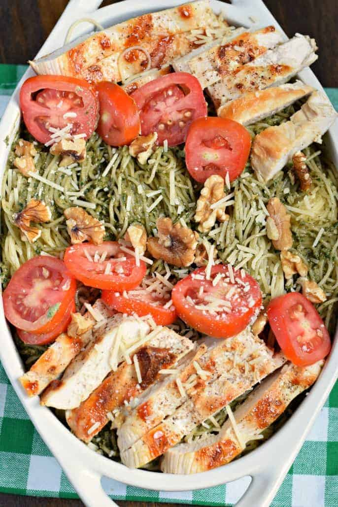 Oval white baking dish filled with pesto pasta, grilled chicken, sliced tomatoes, walnuts, and parmesan cheese.