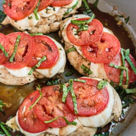 Skillet with chicken, tomatoes, cheese, and basil.