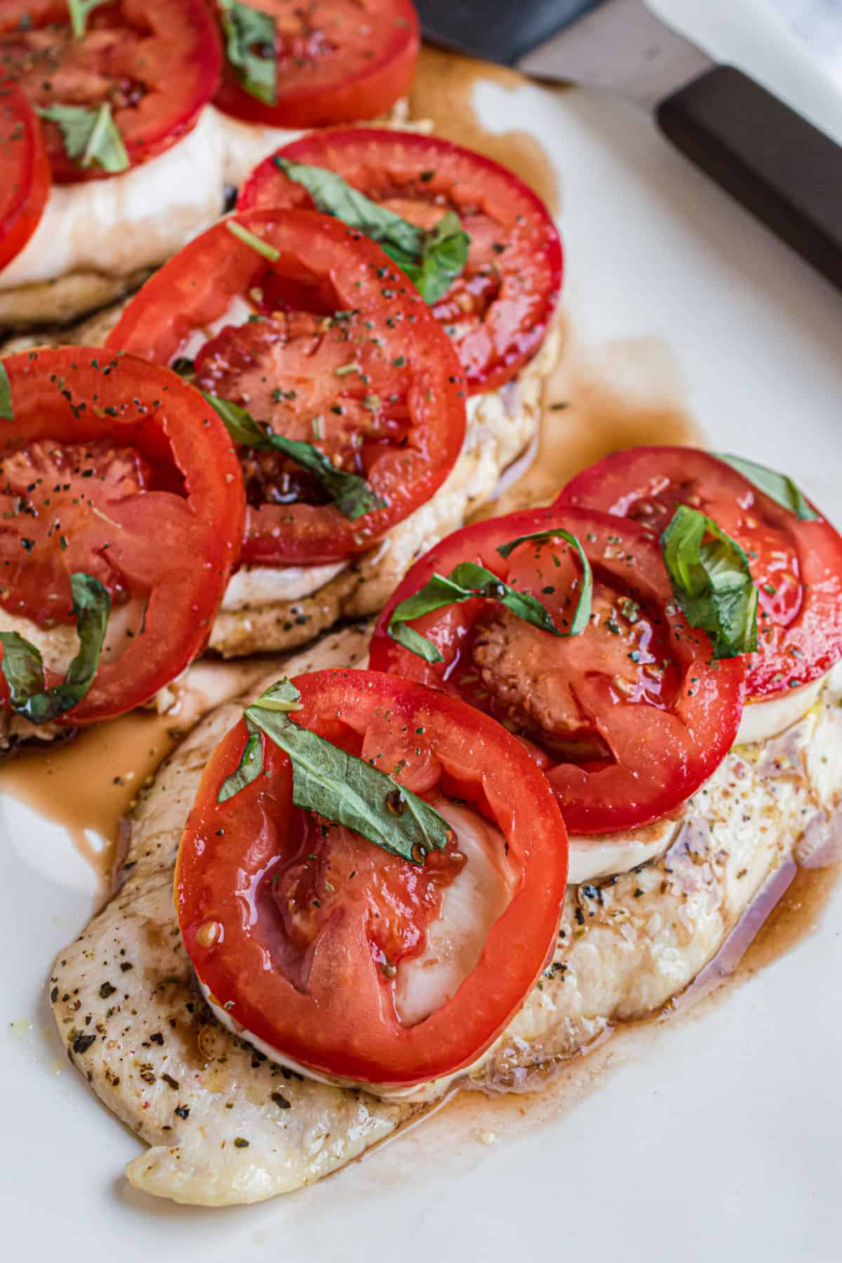 Chicken caprese on a white serving platter.