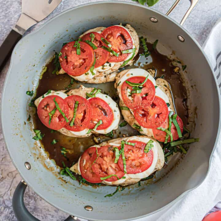 Caprese Chicken Skillet - Delicious pan seared chicken topped with mozzarella, tomatoes, basil and balsamic. This dinner has a gourmet flair and is ready in just 15 minutes!